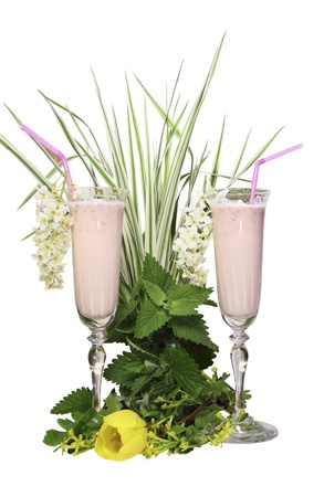 tubules: Glass glasses with a dairy cocktail and tubules on a white background with green leaves and a grass