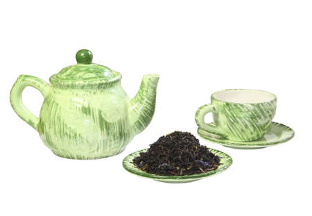 A green teapot, a mug and black tea on a saucer