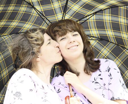 Mother kisses the daughter under a checkered umbrella Stock Photo - 9681991