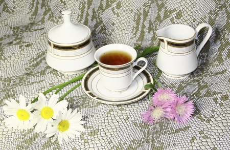 A tea mug  a sugar bowl with camomiles and pink wild flowers  photo