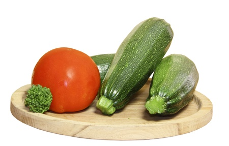 Cabbage of a broccoli and vegetable marrows on a wooden plate on a white background