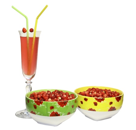 Two round plates with berries of wild strawberry and a glass of juice with tubules for a cocktail on a white background photo