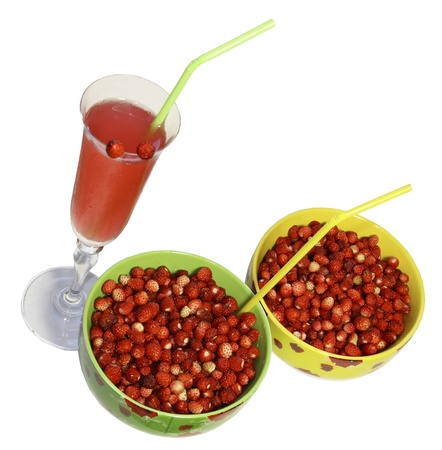tubules: Two round plates with berries of wild strawberry and a glass of juice with tubules for a cocktail on a white background Stock Photo