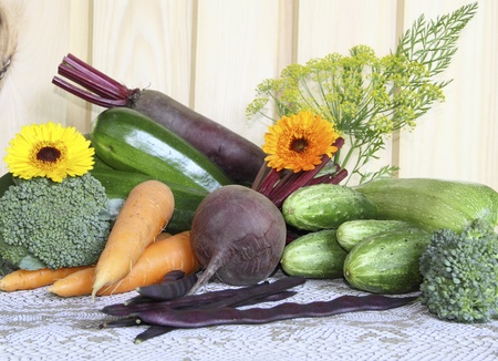 Fresh vegetables against a wooden wall on a grey cloth      photo