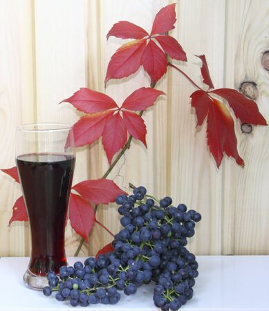 A glass with wine and grapes against red leaves  Stock Photo - 10751979