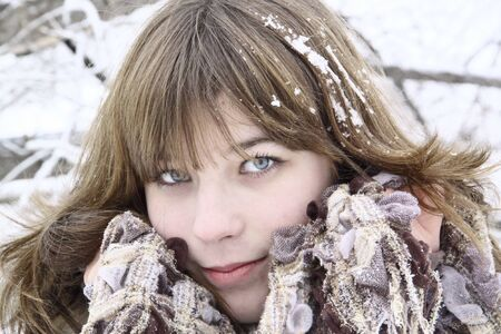 The beautiful girl with a scarf and snow on hair  Stock Photo