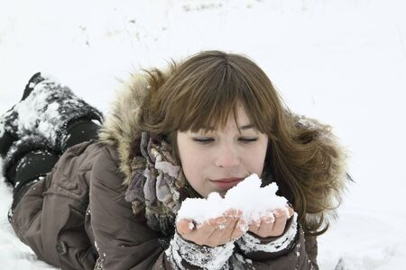 lays: The beautiful girl lays with snow in hands Stock Photo