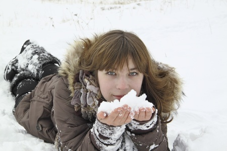 The beautiful girl lays with snow in hands Stock Photo