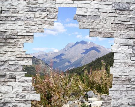 A mountain landscape in a window behind a stone wall  Stock Photo