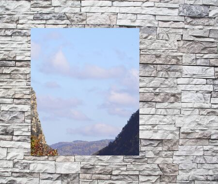 A mountain landscape in a window behind a stone wall  photo