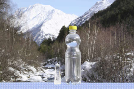 A bottle of pure water c a crystal against majestic top  Stock Photo