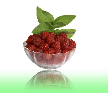 Berry raspberries in a glass vase with the leaves of mint on a white background with a reflection Stock Photo