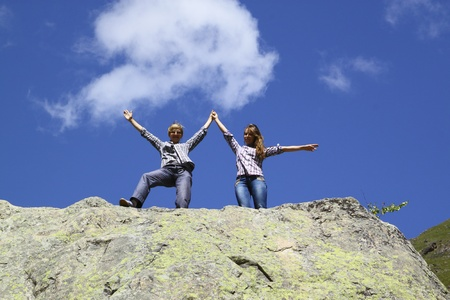 Happy mother and daughter standing on a huge rock, raising his hands up