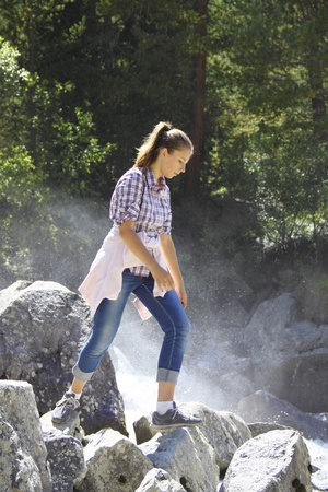 Young girl goes on the rocks by a mountain river Stock Photo