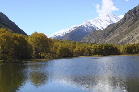 A beautiful lake with yellow trees on the beach and snow-capped peaks in the distance Stock Photo