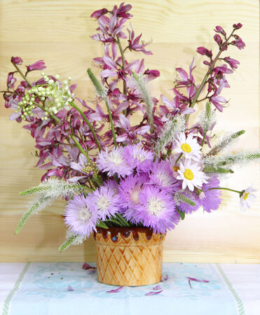 Lovely bouquet of wild wildflowers is in a vase on a wooden wall background  photo