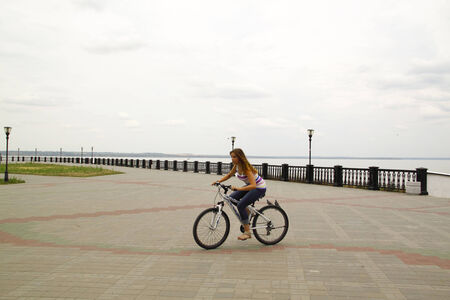 Cute young girl rides a bicycle on the Square