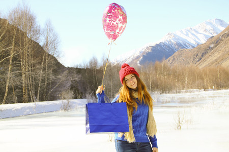 cheerful girl with a balloon and a package with a gift on the background of snowy mountains