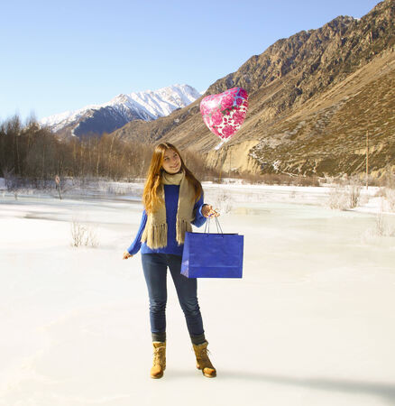 Happy girl with a balloon and a package with a gift on the background of snowy mountains photo