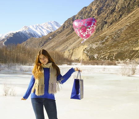Happy girl with a balloon and a package with a gift on the background of snowy mountains Stock Photo