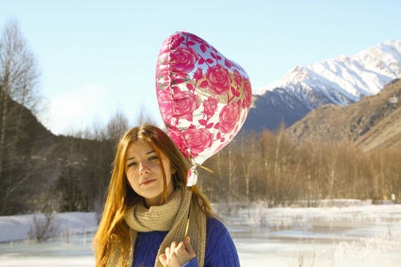 portrait cheerful girl with a balloon and a package with a gift on the background of snowy mountains photo