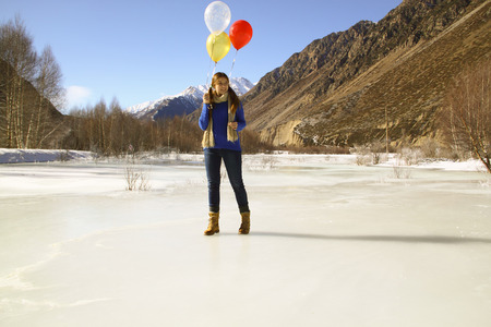 Fun girl with balloons on the hair on the background of snowy mountains Stock Photo