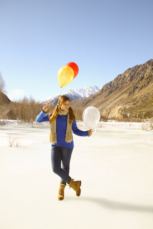 Funny girl with balloons on the hair on the background of snowy mountains
