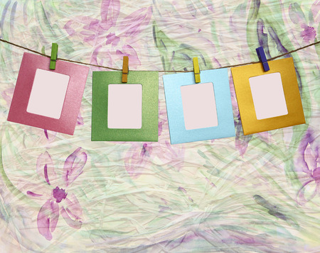Colorful paper frame with clothespins on floral abstract background Stock Photo