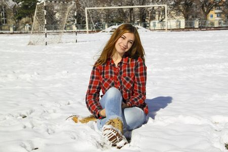 Happy young girl sitting on the snow in the park on a sunny winter day