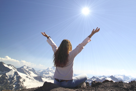 Winning success woman happy with her hands raised above the head in celebration of reaching the top of a mountain during a camping trip, the concept of freedom