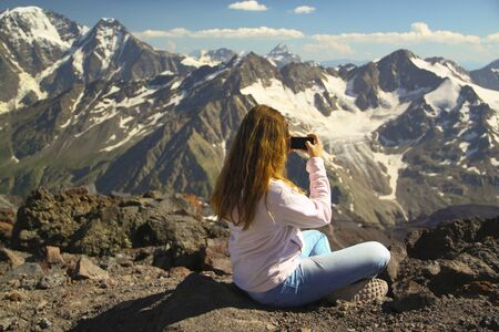 Girl sits on the top of the mountain and take pictures on the phone during a hiking trip, the concept of freedom Stock Photo