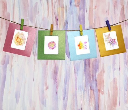 clothes pegs: Beautiful watercolor flowers within a clothes pegs on an abstract watercolor background Stock Photo