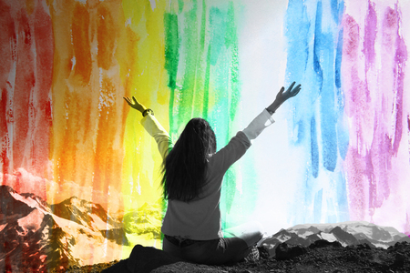 arms above head: Woman with arms raised above the head, double exposure with rainbow watercolor background in celebration of reaching the top of the mountain during the campaign, freedom concept