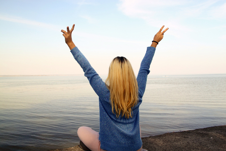 Young girl with arms raised above the head on the shore of the sea, freedom concept