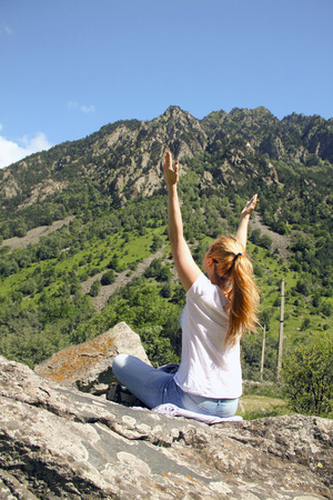 Woman with arms raised above the head, in celebration of reaching the top of the mountain during the campaign, freedom concept
