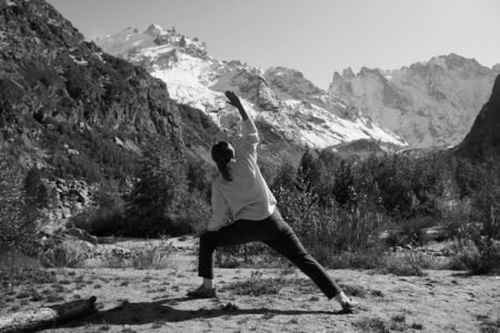 Woman practices yoga in a mountain gorge. Travel Lifestyle Relaxation. Emotional concept. Outdoor adventure. Harmony with nature. Banco de Imagens