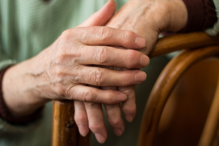 artrite: due mani di una donna anziana seduta su una sedia