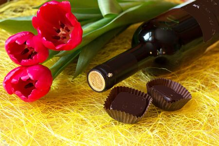 a bottle of wine, chocolates and three red tulips on a yellow background