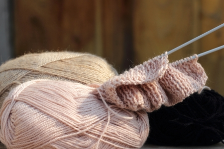 started needlework of pink woolen threads on the table photo