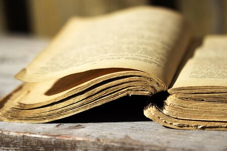 yellowed: yellowed page of an old book lying on the wooden board Stock Photo