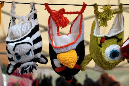 knitted hats hanging on a rope for sale