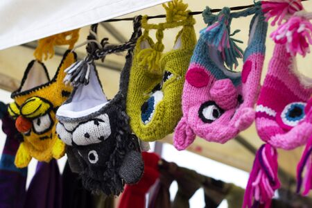 funny knitted from colored yarn hats hanging on a rope