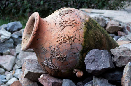 old cracked clay vase lying on the rocks