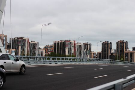 cars go on the road to a new young city with beautiful tall buildings