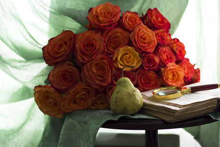 A bouquet of flowers, a book with a magnifying glass and a pear lie on a table