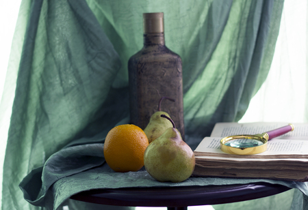 A book with a magnifier and pears and an orange lie on a table