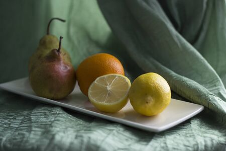 Delicious fruits lie on a ceramic plate on a table