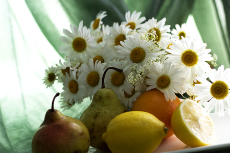 A bouquet of chamomiles, a lemon, an orange and pears on a table Reklamní fotografie