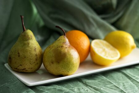 Lemon, orange and pears lie on a white ceramic plate on a table