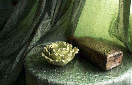 Candlestick and handmade bottle on a green background Reklamní fotografie